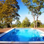 Inground swimming pool with wooden deck and glass fence