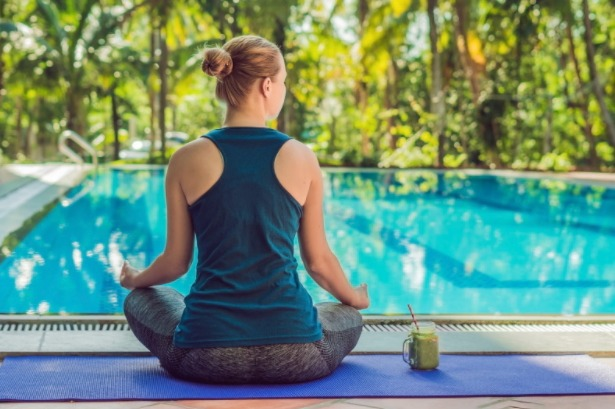 A girl is doing meditation in front of swimming pool
