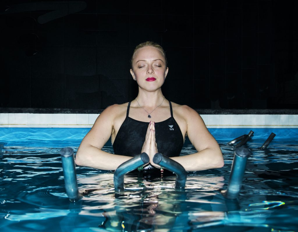A girl is doing meditation in swimming pool