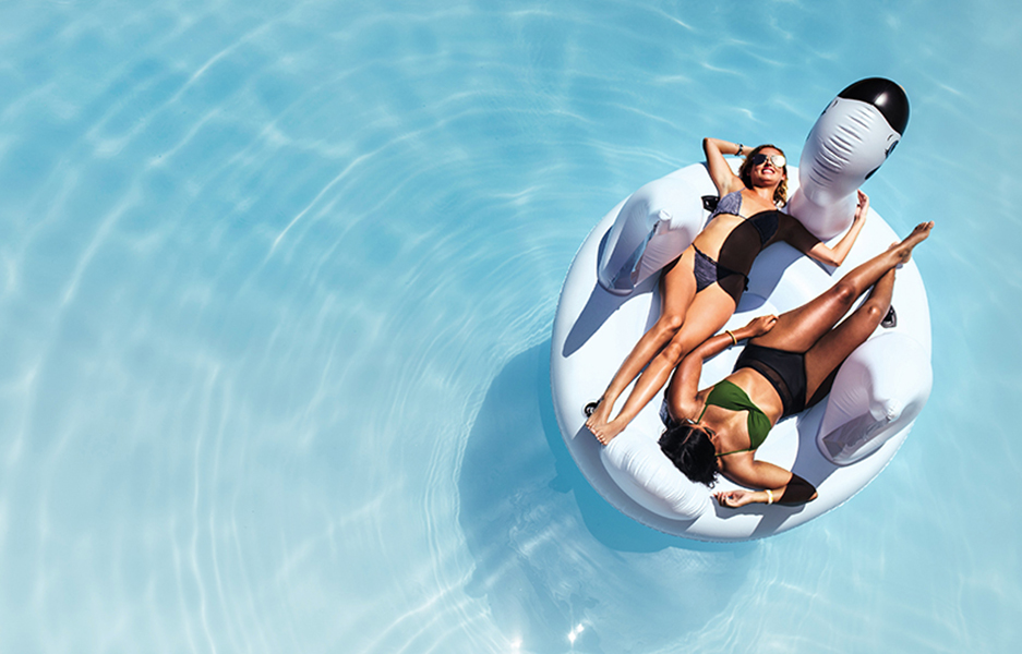 Overhead view of two women in bikini lying down on an inflatable toy in swimming pool. Girls sunbathing on floating pool inflatable toy.